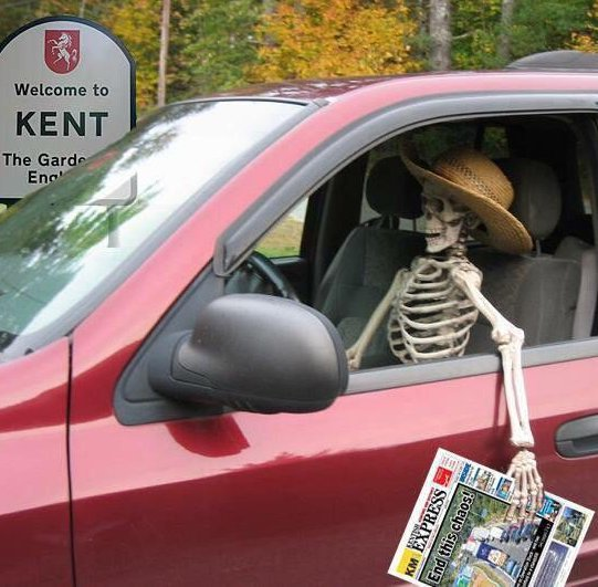 "A red car with a skeleton in the driving seat, holding a copy of the Kentish Express in its 'hand' with a picture of a queue of trucks and the headline ""End this chaos!"". Behind the car is a sign saying ""Welcome to Kent, the garden of England""."
