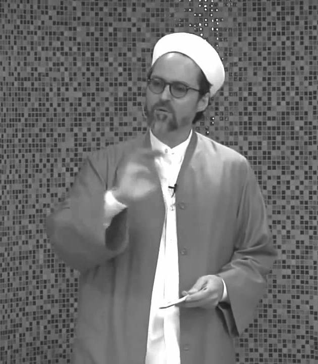 Black and white picture of Hamza Yusuf, a middle-aged White man wearing a white turban on his head, with a white shirt with no tie, and a dark-coloured jacket over it. He is standing against a wall decorated with small tiles.