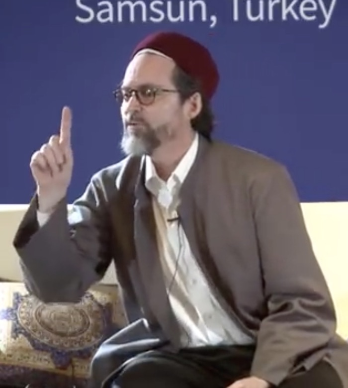 "Picture of Hamza Yusuf, a white man with a short, greying beard wearing a white shirt with a grey jacket over it and a red felt cap, with his right index finger raised. He is sitting on a beige sofa with cushions. Against the blue background is written ""Samsun, Turkey""."