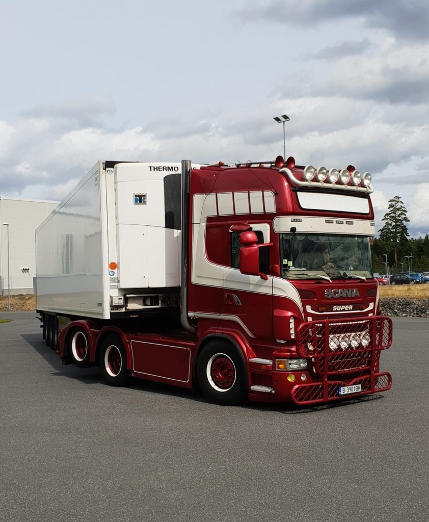 A maroon Scania V8 tractor unit with ten added headlights and bull-bars. The tractor has a long wheelbase and a rear tag (lifting) axle. It is pulling an unmarked white refrigerated trailer with a Thermo King fridge device. The truck is photographed mid-turn on a large expanse of tarmac on an industrial estate.