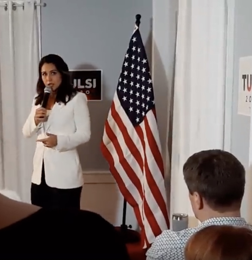 "Picture of Tulsi Gabbard, a woman of South Asian appearance with light brown skin and shoulder-length black hair, wearing a fitted white jacket over a black skirt or pair of trousers, standing in front of a small sign saying ""Tulsi 2020"" with an American flag hanging from a pole next to her."