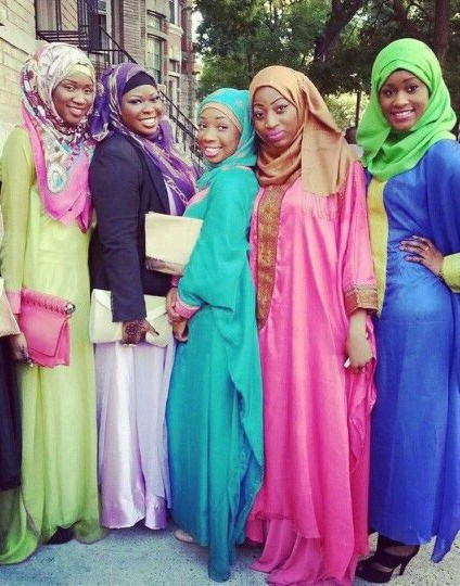 Five young Black women wearing different coloured long dresses and headscarves.