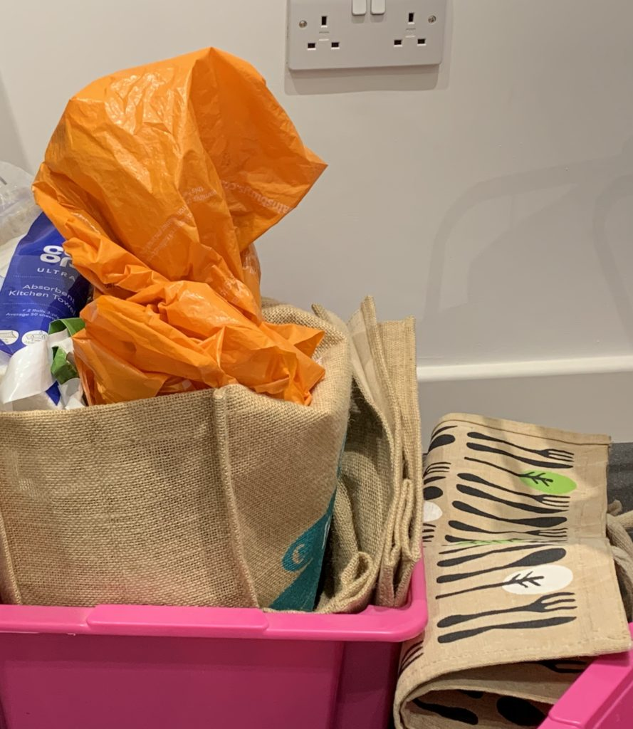 A collection of jute and orange plastic bags in two pink plastic crates.