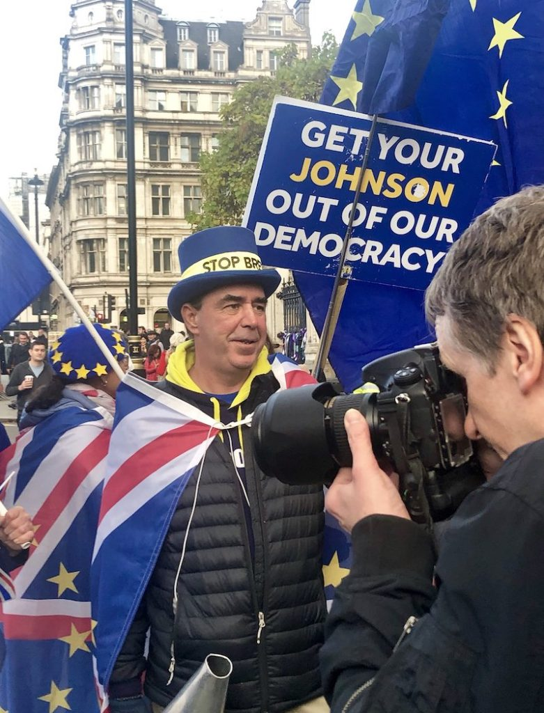 "On Piccadilly outside Green Park, London. A picture of a middle-aged white man wearing a blue rimmed hat with a yellow ribbon round it which says ""Stop Brexit"", and next to him someone is holding up a banner that says ""Get your Johnson our of our democracy"". Several EU and British flags are on display."