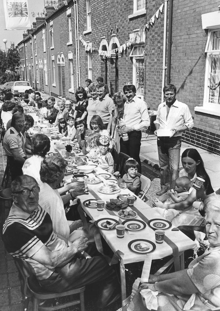 Black and white pictures of a row of tables with many men, women and children of all ages sat at them, with plates and cups and food on the tables. Flags are hung from the red-brick houses which open directly onto the streets.
