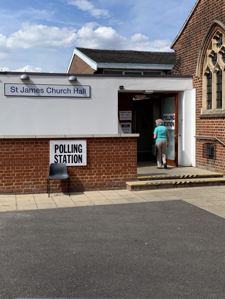 "A polling station in a hall at the back of an English church; an old lady is walking through the door. A plastic chair sits in front of a sign saying ""polling station""."