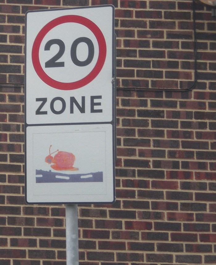 A sign with the number 20 in a red circle on a white background with 'zone' underneath in bold Swiss type; under that is a child's drawing of a red snail. Behind the signpost is a red brick wall.