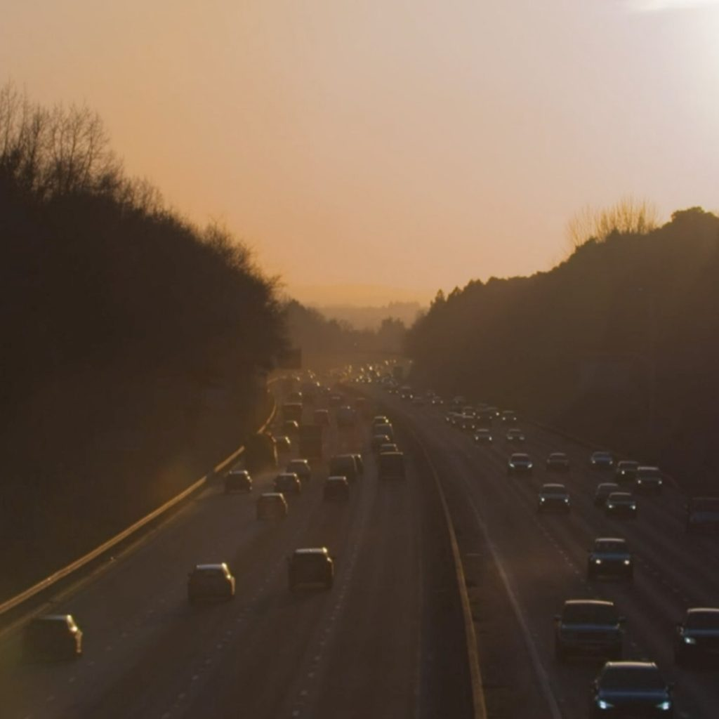 A motorway with four lanes and no hard shoulders with trees on either side, with hills in the distance, with the sun in the top-right corner.