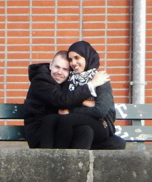 A white man and a light brown-skinned Middle Eastern or South Asian woman sitting on a park bench together; the man's right hand is on the woman's left shoulder. The man is wearing black with a hood (perhaps a hoodie or a Moroccan thobe) while the woman is wearing black or dark grey clothing and a black scarf over her head and a black and white scarf around her neck. There is a low stone wall in front of them and a red brick wall behind them with a metal pipe running vertically down it.