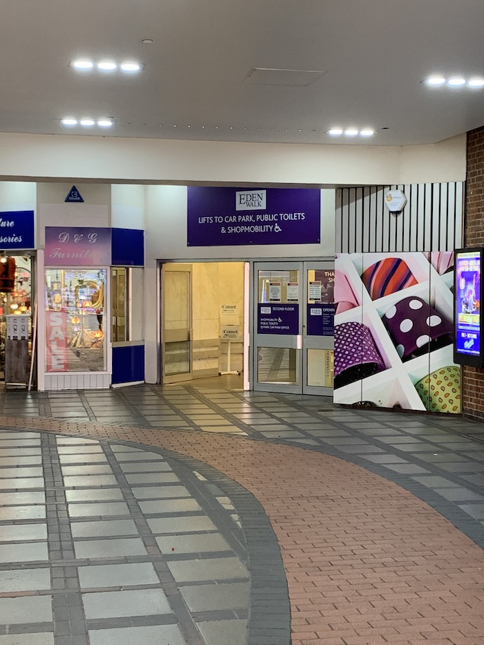 "A doorway in a covered shopping arcade, with a sign over it saying ""Eden Walk: lifts to car park, public toilets and shopmobility""."