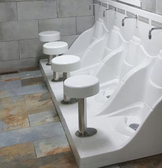 A row of four ablution areas with a white stool in front of a white ceramic sinks with a tap over the top of each, with a drain at foot level. There are slate tiles on the wall and marble tiles on the floor.