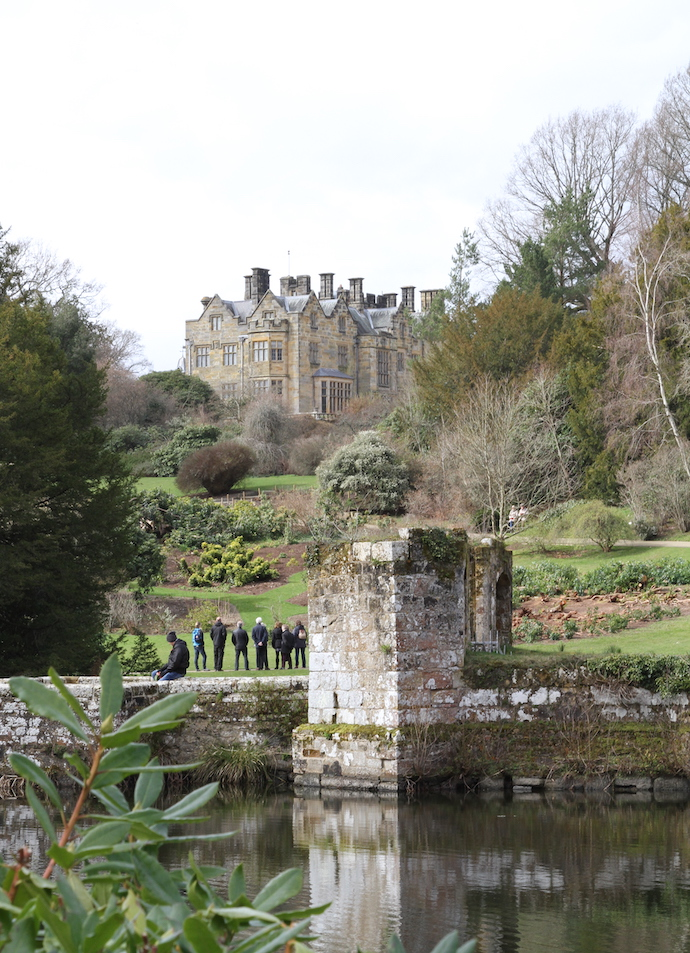 A view from across a small pond, across a garden on a hill to a large three-storey 19th-century mansion.