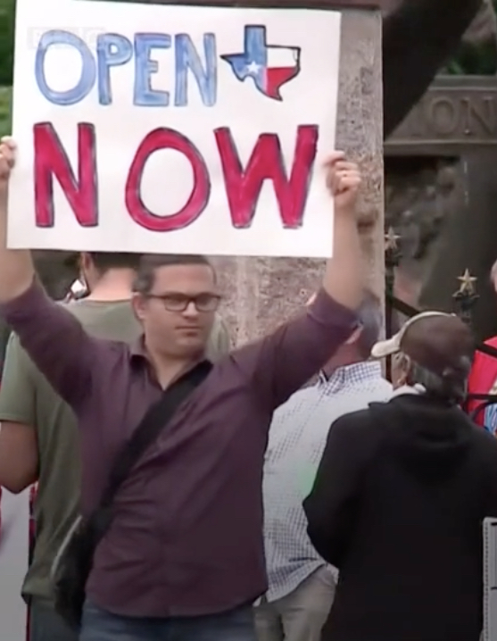 "A young, white man with spectacles holding a sign saying ""Open Now"" with a map of Texas between the two words."