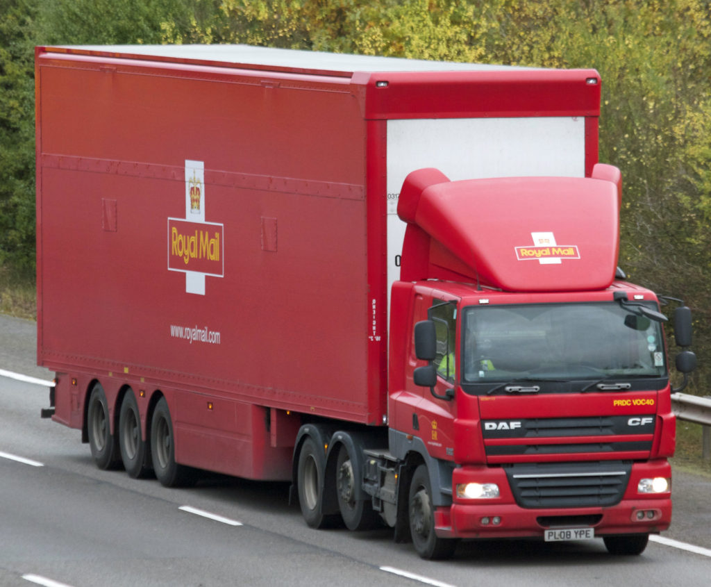 A red articulated lorry with the Royal Mail logo on the side with a double-deck trailer on a motorway.