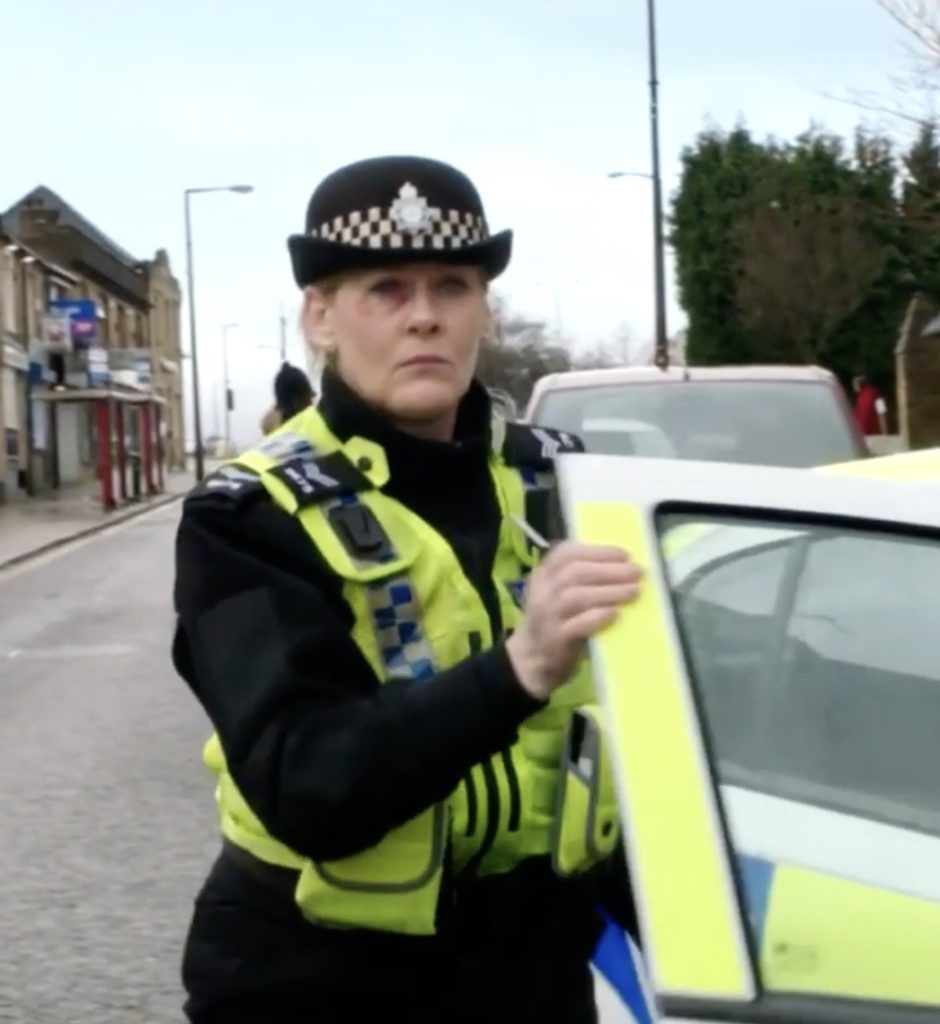 Picture of a middle-aged white woman wearing a black police uniform and hat and police-issue high-visibility waistcoat, getting out of a police car on a street with shops along one side.