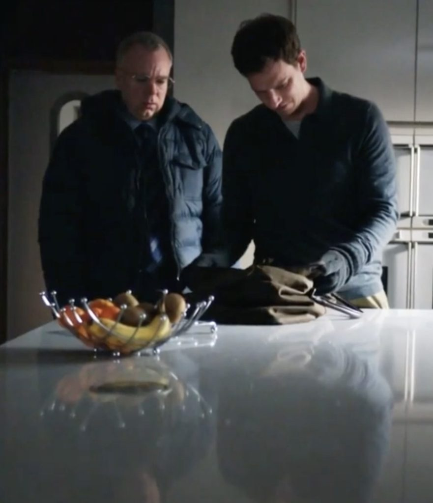 Still of two white men, one in his 50s and the other in his 30s, wearing dark coloured jackets, looking into a bag which is on a kitchen table. A glass bowl containing bananas and other fruit is in front of them.