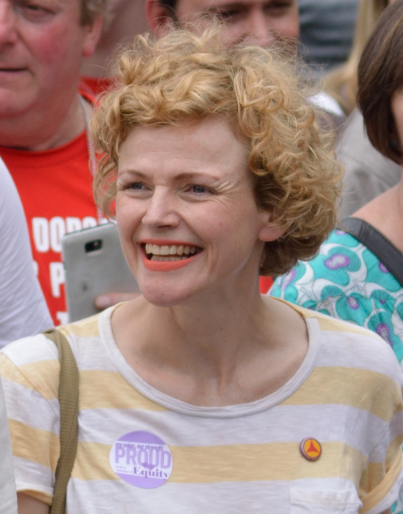 "Picture of Maxine Peake, a middle-aged white woman with curly fair hair, wearing a yellow and white striped T-shirt with a sticker saying ""My union, our strength; proud to be a member of Equity"" (the actors' union). There is a crowd of people behind her."