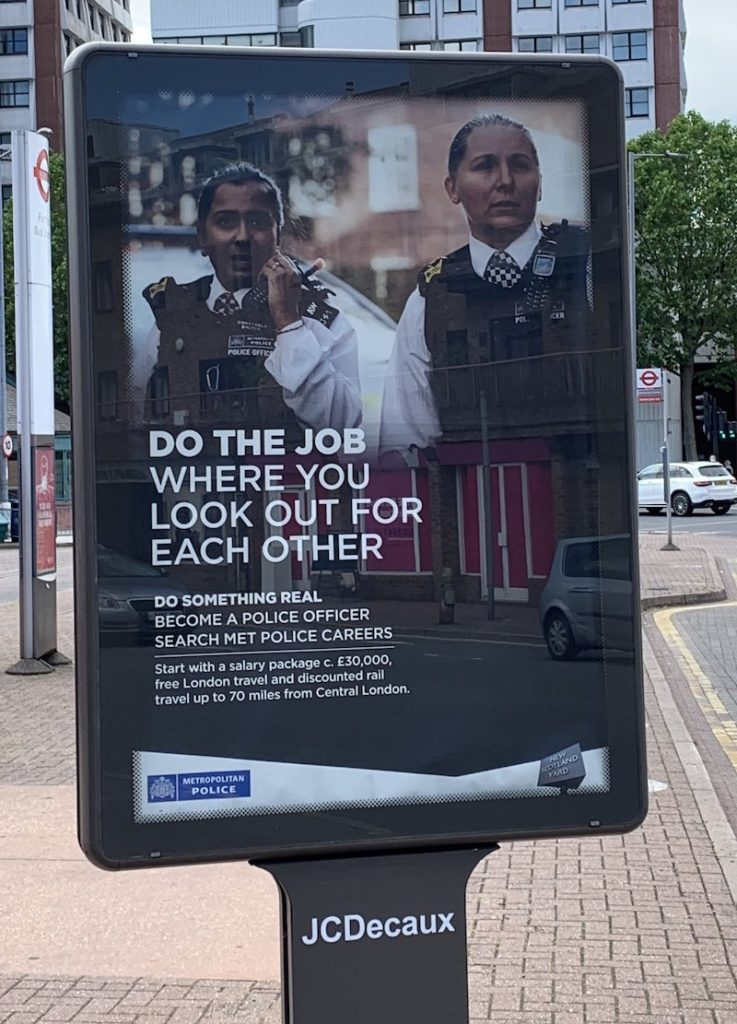 "A police recruitment ad from the Metropolitan Police which shows two officers, one a white woman and the other Asian and probably male. The text reads ""Do the job where you look out for each other. Do something real. Become a police officer."""