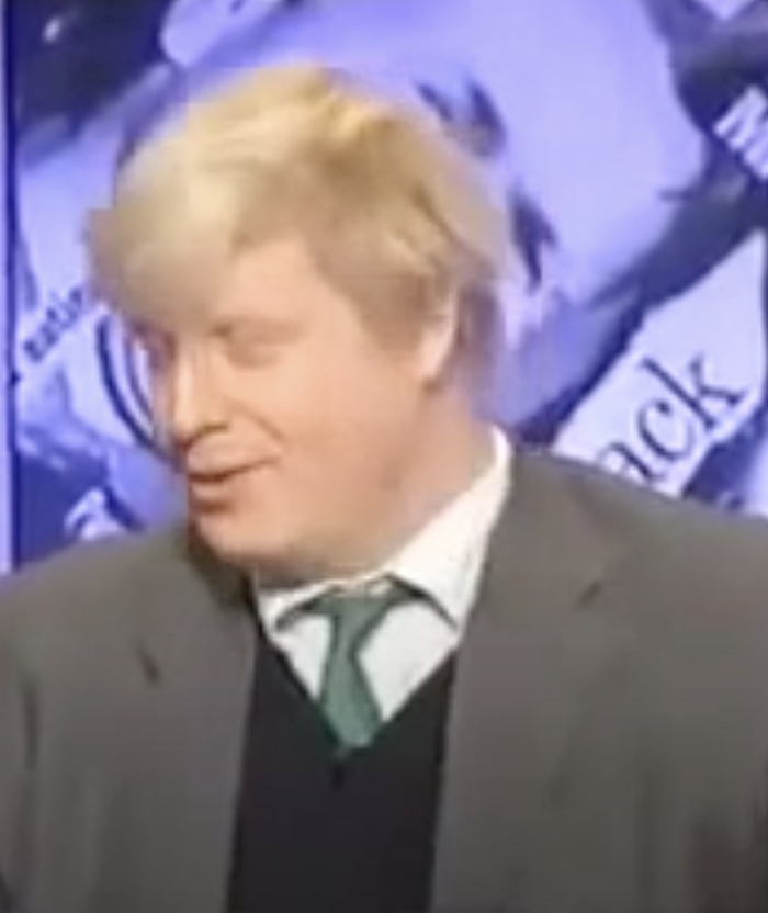 A still from a 1999 edition of Have I Got News For You, showing Boris Johnson sitting in front of a backdrop consisting of British newspaper cuttings from the time.