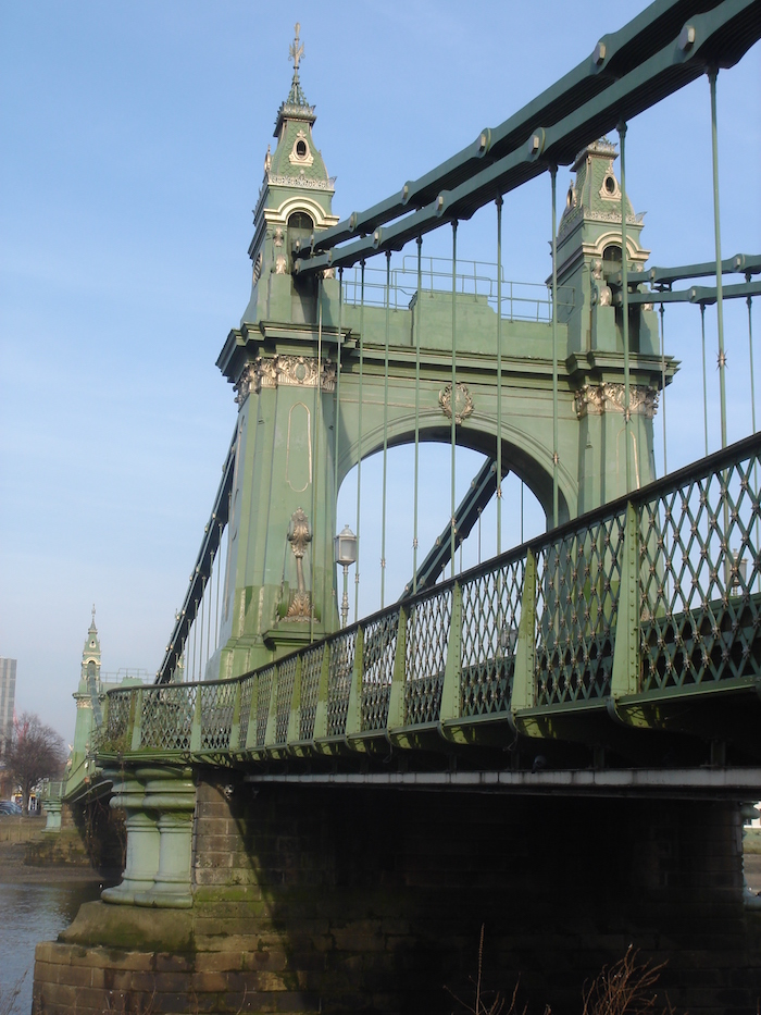 A suspension bridge over a river with towers, archway and supports painted green. The sky is blue.