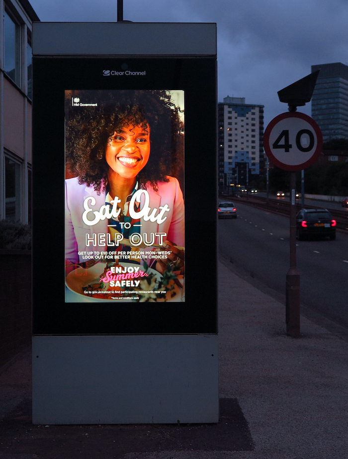 "A picture of an illuminated ""Eat Out to Help Out"" poster featuring a Black woman holding a plate of food. The poster is next to a 40mph speed limit sign on a dual carriageway; it is twilight and headlights can be seen."