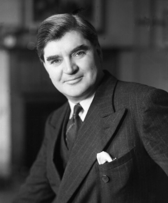 Black and white picture of Aneurin Bevan, a clean-shaven, middle-aged white man wearing a dark grey suit and tie.
