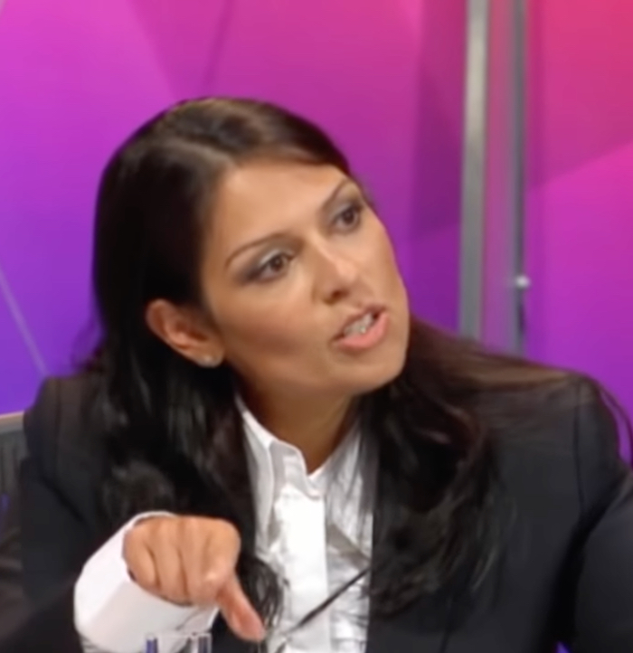 Priti Patel, a South Asian woman in her 40s wearing a white shirt open at the neck under a dark grey suit jacket, pointing her finger forwards. Behind her is a BBC background of different shades of pink and purple.