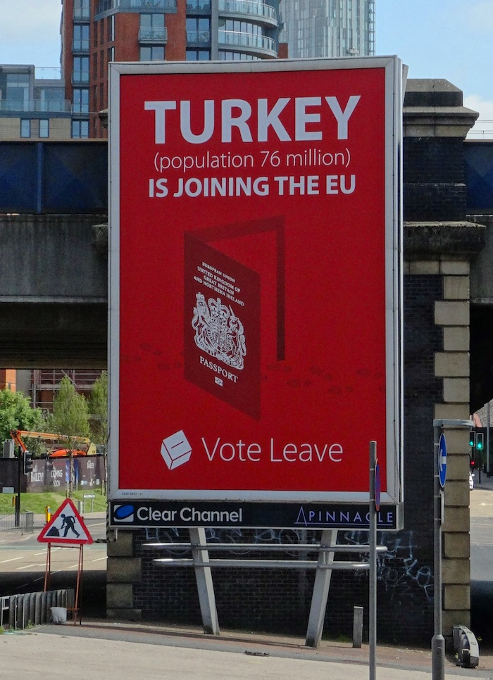 "A poster on a billboard that reads ""Turkey (population 76 million) is joining the EU. Vote Leave"" with a picture of an open door with a British passport displayed on it, with footsteps passing through it. The Pinnacle/ClearChannel billboard appears in front of a railway bridge."