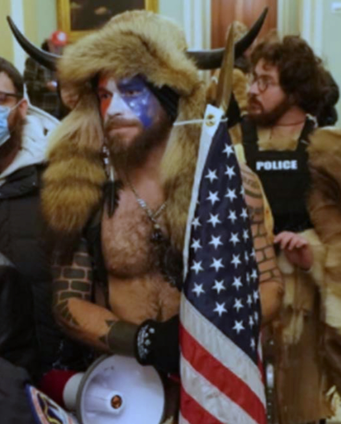 Picture of a youngish white man with a mostly bare, hairy chest, dressed in a furry headpiece which drapes partly over his chest, which has horns; he has tattoos on his arms, his face has US flag paint and he is carrying an American flag. Behind is a bearded, long-haired white man wearing a police body shield (whether legitimate or stolen is not clear).