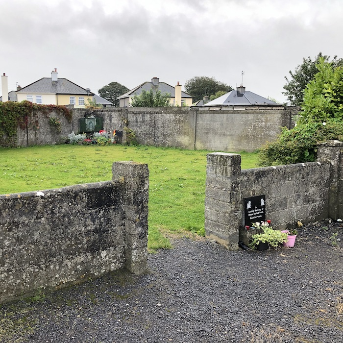 """A small garden (underneath which is a mass grave of babies). In the foreground is a stone wall with a gap for an entrance; on the ground next to it is a sign which reads """"In loving memory of those buried here; rest in peace"""". There are some flowers next to it. In the opposite corner of the garden is a shrine with a statue of the Virgin Mary and a larger deposit of flowers."""