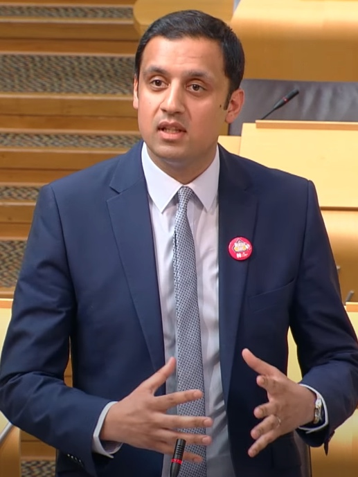 Image of Anas Sarwar, a clean-shaven South Asian man wearing a dark blue jacket over a white shirt and silver and grey tie.