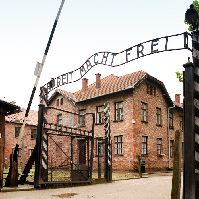 "The gateway to the Auschwitz concentration camp with a metal sign overhead reading ""Arbeit macht frei"" (work liberates). Behind the gates are the red-brick former Austrian barracks buildings."