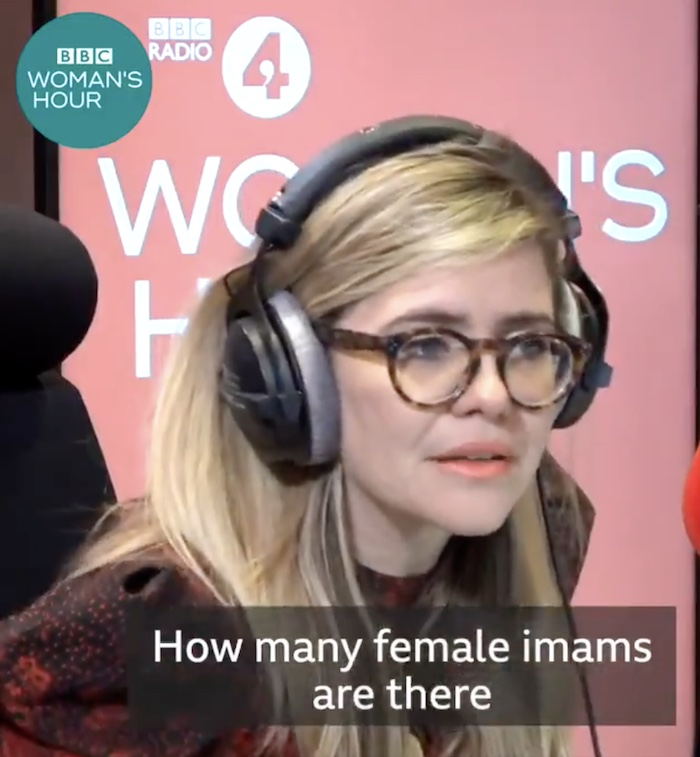 """A still of Emma Barnett, a young white woman, wearing headphones and speaking into a large red studio microphone. Behind her is a back-lit pink backdrop with he words """"BBC Radio 4 Woman's Hour"""" on it. A caption reading """"How many female imams are there?"""" appears at the bottom of the image."""
