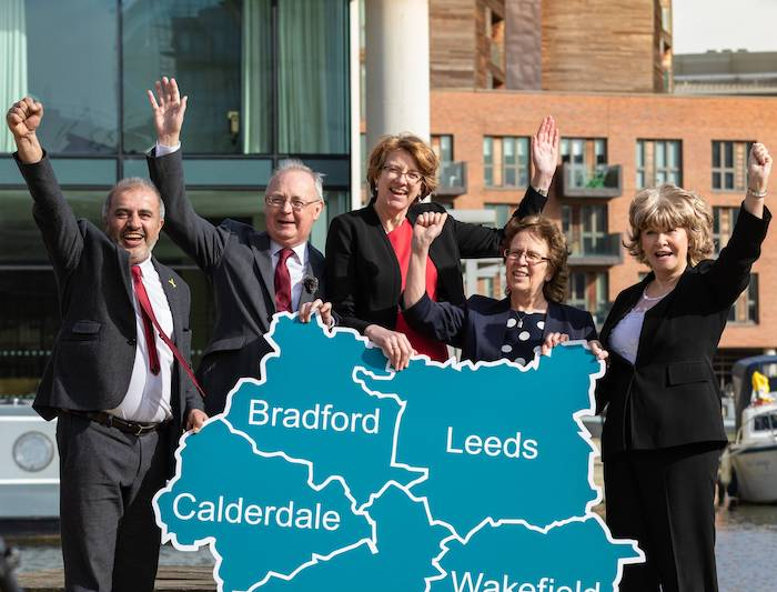A group of five middle-aged to elderly people (one South Asian man, one white man and three white women) holding up a map of West Yorkshire with the five boroughs (Leeds, Bradford, Calderdale, Kirklees and Wakefield) marked. Behind them is a river with two boats visible, and a plate glass building behind to the left and a red brick building behind to the right.
