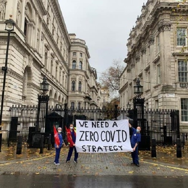"A picture of three or four men wearing masks, holding up a sign saying ""We need a Zero Covid strategy"", on a rainy day outside Downing Street, London."