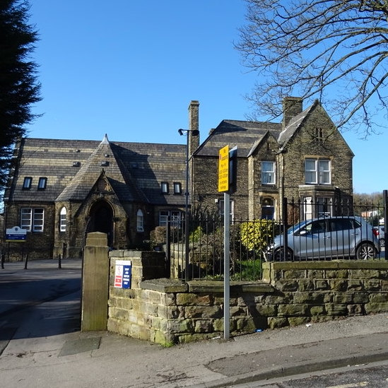 A 17th-century stone school building behind a low stone wall. A silver-grey hatchback car can be seen behind the railings. A yellow parking restrictions sign is in front of the railing.