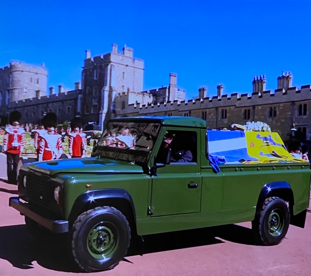 a green open-backed Land Rover. His coffin (draped with his coat of arms) lies in the open back. Soldiers in formal uniforms can be seen behind the hearse in the grounds of Windsor Castle, the turreted walls of which can be seen in the background.