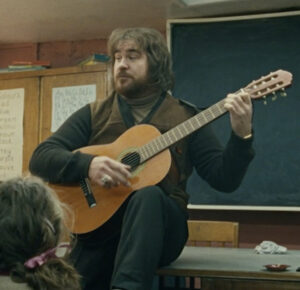 A long-haired, bearded white man sits in front of some pupils strumming a classical guitar. Behind him is a blackboard and a cupboard with some learning materials stuck to the doors.