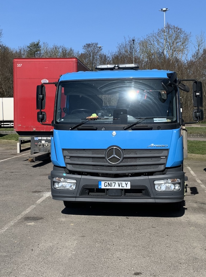 A picture of the front of a blue Mercedes-Benz Atego truck in a parking bay. Next to it is a red Cartwright drawbar trailer without its leading vehicle.