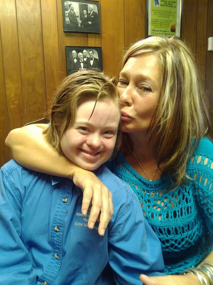 Picture of Jenny Hatch and Kelly Morris, two white women with blonde hair; Hatch has Down's syndrome. Kelly has her arm round Jenny and is kissing the side of her face. They are standing in front of a wood panelled wall with two small pictures on it.