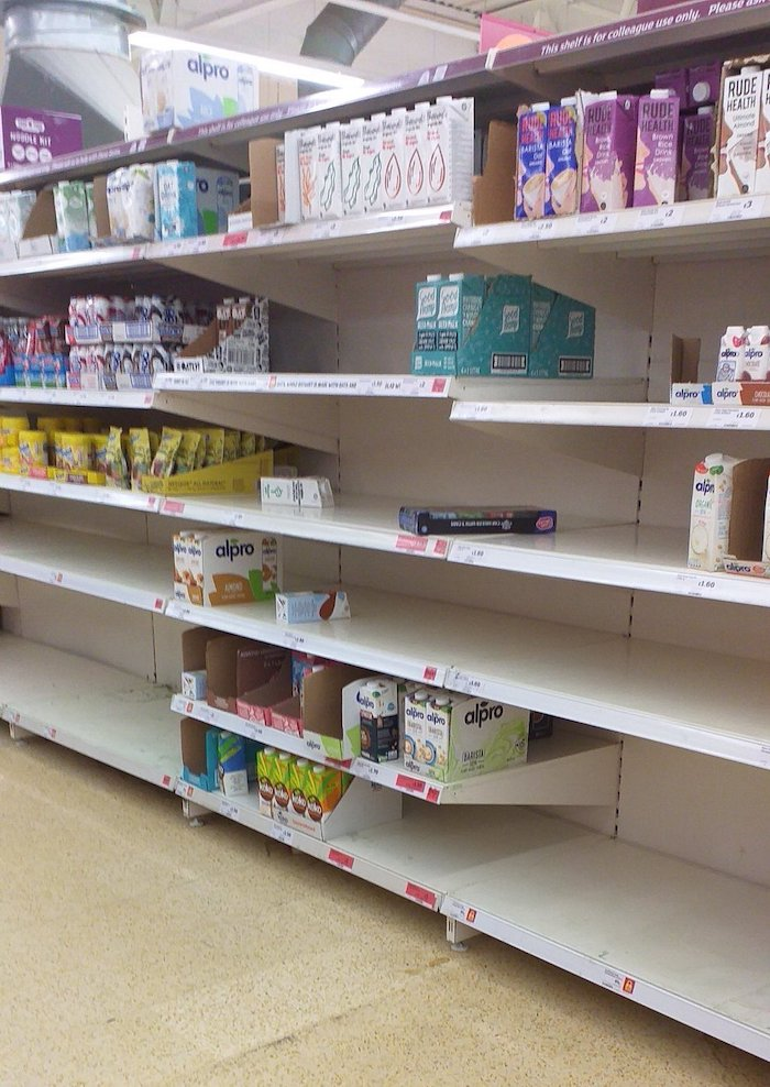 A section of a Sainsbury's store where the shelves of milk substitutes are either sparsely-stocked or empty.
