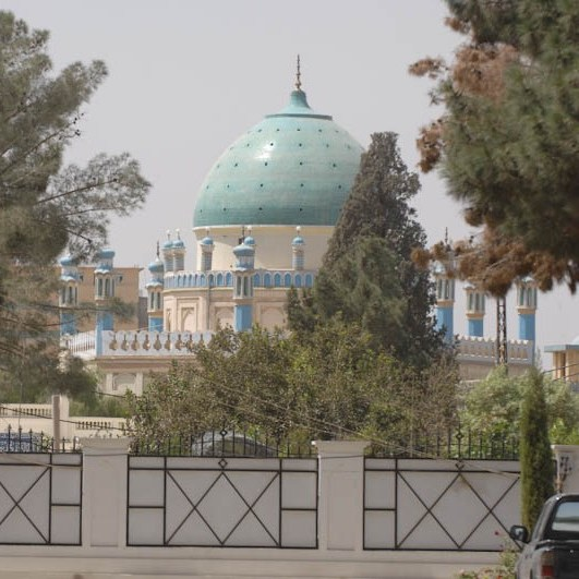 A mosque with a turquoise dome with terraces surrounding it painted pastel blue, with miniature and full-size minarets. What look like pine trees of some sort can be seen in the foreground, partly obscuring the mosque.